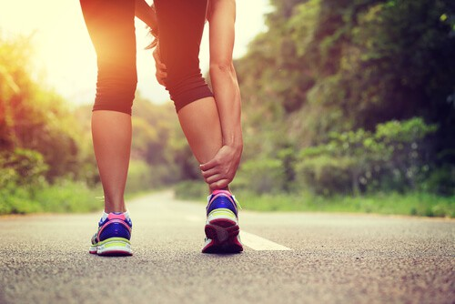 woman holding calf and ankle sprain after running