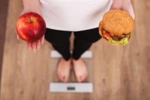 person on scale with healthy and unhealthy food options