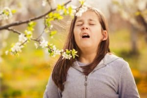 seasonal allergies make girl sneeze