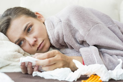 woman sick with tissues during flu season