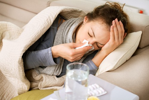 cold and & flu symptoms make woman rest